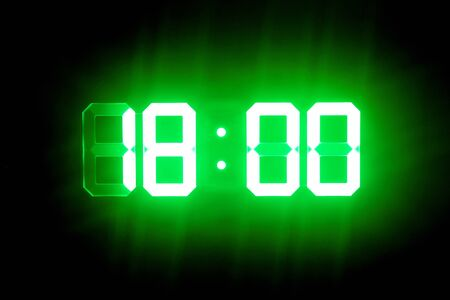 Green glowing digital clocks in the dark show 18:00 time Stock Photo