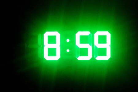 Green glowing digital clocks in the dark show 8:59 time