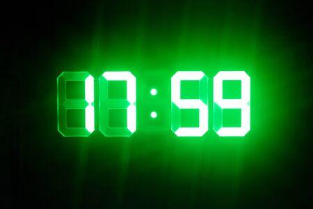 Green glowing digital clocks in the dark show 17:59 time