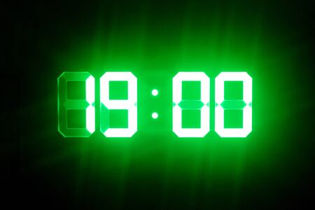 Green glowing digital clocks in the dark show 19:00 time