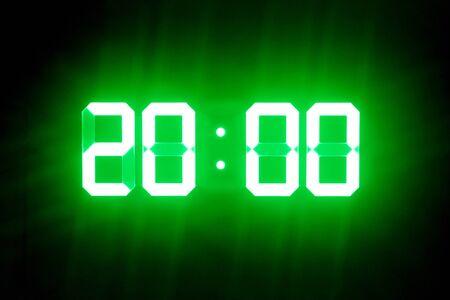 Relojes digitales verdes que brillan intensamente en la oscuridad muestran 20:00 hora
