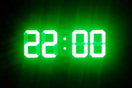Green glowing digital clocks in the dark show 22:00 time