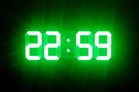 Green glowing digital clocks in the dark show 22:59 time Stock Photo