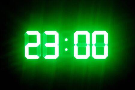 Grün leuchtende Digitaluhren im Dunkeln zeigen 23:00 Uhr Standard-Bild