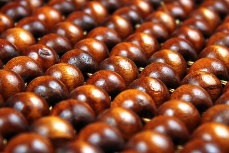 Wooden beads rug. Hand made car seat. Natural varnished wood background. 免版税图像