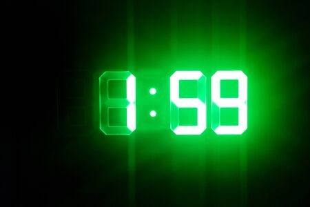 Green glowing digital clocks in the dark show 1:59 time Stock Photo