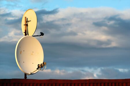 Two satellite dish antennas on a roof