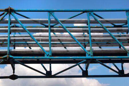Old metal overhead pedestrian footbridge against blue sky
