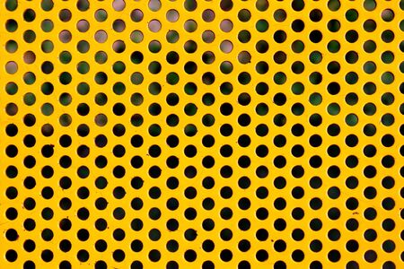Round holes in yellow perforated metal plate.