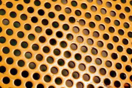 Round holes in yellow perforated metal plate