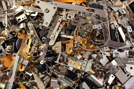 Pile of shiny metal parts. Scrap polished steel details. Abstract industrial background. Banco de Imagens