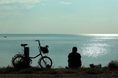 Silhouettes of bicycle and man sitting at the seashore and looking at sea Фото со стока