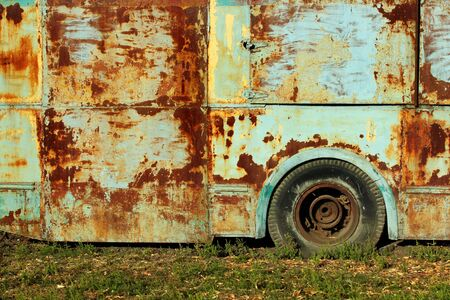 Old rusty bus on green grass Фото со стока