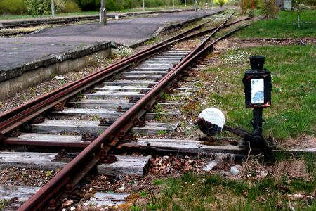 Abandoned railway station. Rusty rails and old switch. Фото со стока