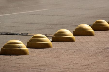 Round concrete bollards at a parking lot