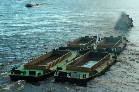Tug boat tows empty barges, filled with water to pass under low bridges