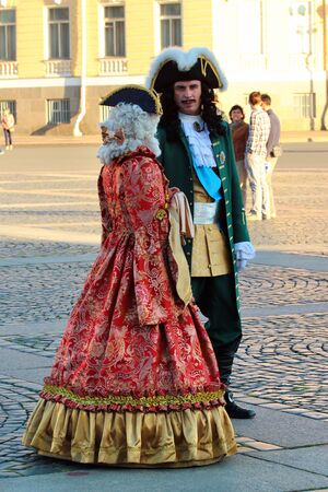 Saint Petersburg, Russia - July 4, 2017: Actors on Palace Square disguised as Tsar Peter the Great and other noble people of the royal family invite tourists to a fancy-dress photo session.