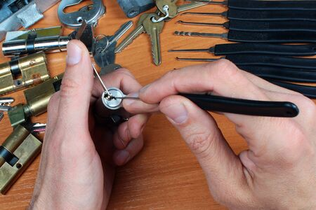 Locksmith picks a cylinder lock with lockpick and tension wrench Фото со стока