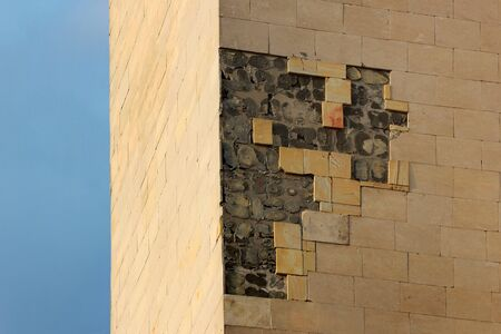 Broken and fallen off tiles on a building wall