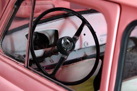 Steering wheel in an old pink car