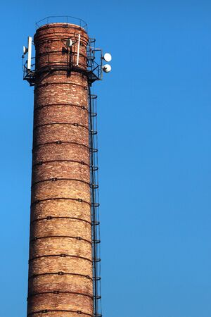 Old brick pipe with antennas against blue sky background Фото со стока