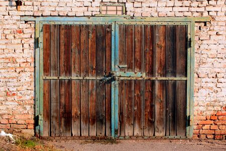 Old wooden garage doors. Flaking paint and rust on gates of abandoned building.
