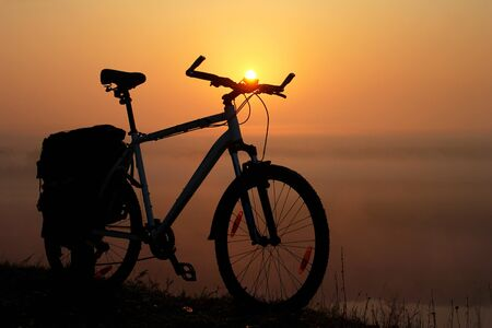 Silhouette of a bicycle against the orange sky at sunrise, with sun as a headlight