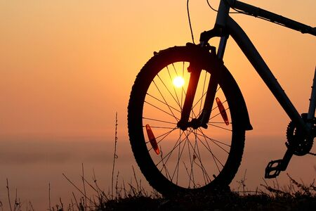 Silhouette of a bicycle against the orange sky at sunrise