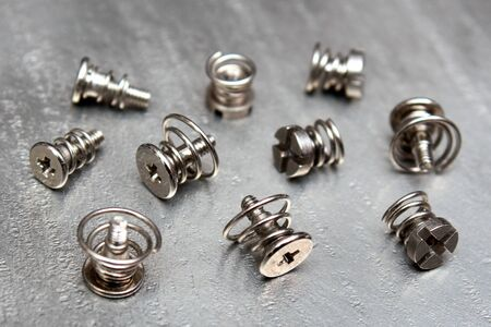 Spring loaded screws on metal plate. Selective focus.