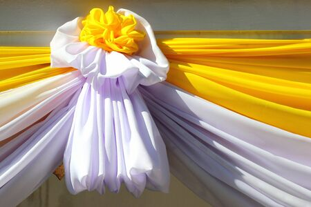 Decorative flower made of yellow and white ribbons, traditional colors of Thailand