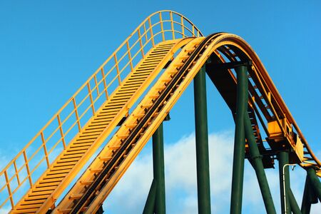 Roller coaster against blue sky background. Amusement park attractions.