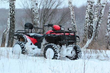 Snow covered ATV in winter forest