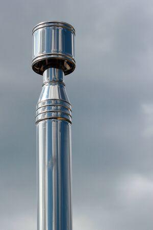Metal chimney against blue sky background