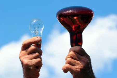 Hands hold infrared lamp and transparent incandescent light bulb against blue sky background