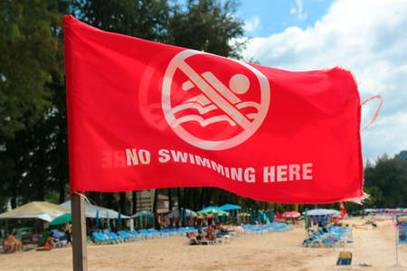 Phuket, Thailand - December 4, 2019: No swimming here sign on red flag at the Kamala Beach, Phuket. Éditoriale