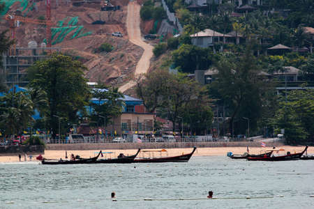 Phuket, Thailand - December 4, 2019: Long tailed boats wait for tourists at the Kamala Beach, a popular place in Phuket island north of Patong city.