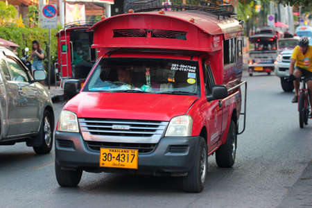 Chiang Mai, Thailand - December 3, 2019: Red songthaew minibuses are one of the city's symbols and a popular transportation in Chiang Mai.