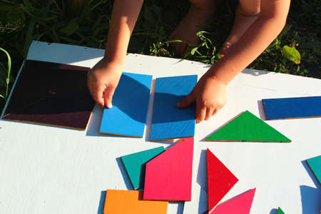 Little boy tries to solve the puzzle, moving different geometric shapes Zdjęcie Seryjne