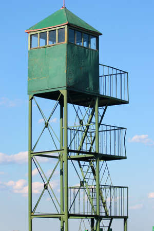 Old metal watchtower against blue sky
