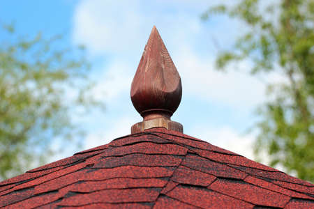 Asphalt shingle and wooden spire on a gazebo roof Фото со стока