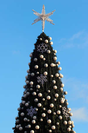 Christmas tree decorated with white balls and stars Фото со стока