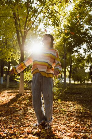 a young girl is playing in the autumn park Stock Photo