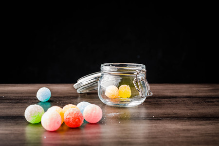 colorful candy in jar and on wooden table