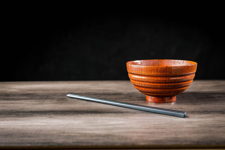 Wooden bowl and chopsticks on the table