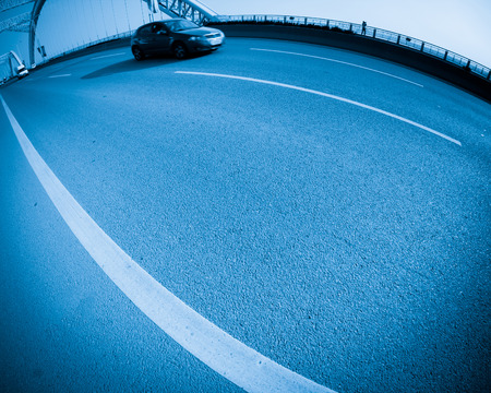 highroad: road through the bridge with blue sky background of a city.