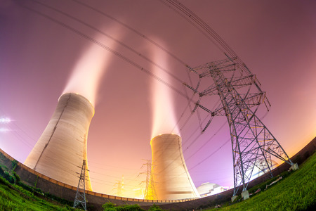 upward view of the cooling towers and high voltage power transmission tower at night photo