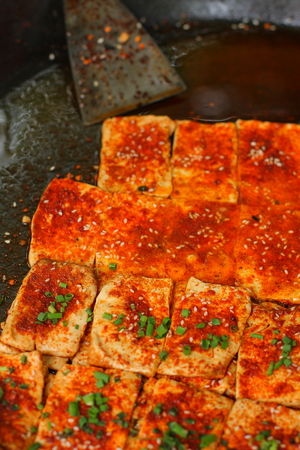 beancurd: Close up of frying beancurd in a big black iron pan. Stock Photo