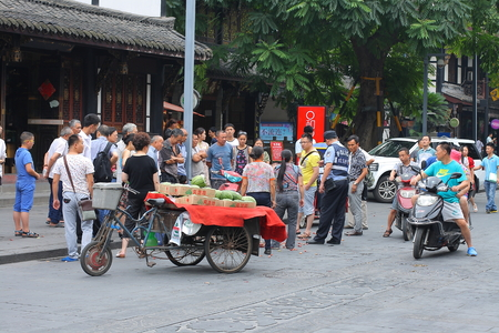 mediate: CHENGDU, CHINA - JULY 5: Crowds watch the argument between a grape seller and buyer, a policeman mediate the dispute, near Wenshu monastery on July 5, 2014,Chengdu, China. Editorial