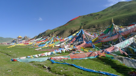 buddhism prayer belief: Colorful prayer flags and Gerisi Temple on Tibetan Plateau, Qinghai, China