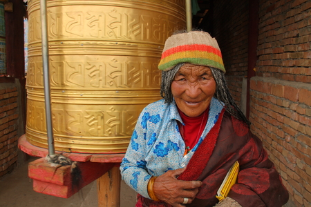 GUOLUO, CHINA - JULY 26: Old Tibetan spends her lifetime in a Tibetan Buddhism Temple on the Tibetan plateau, together with big prayer wheels, July 26, 2013, Guoluo, Qinghai, China